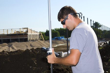 geodesist: Geodesist working at a new village stadium