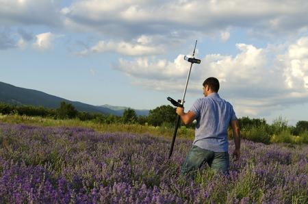 topógrafo: Land surveyor crossing lavender field Foto de archivo