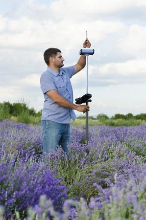 topógrafo: Land surveyor tracing in a lavenerd field