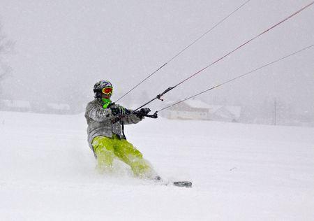 Young men in action snowkiting