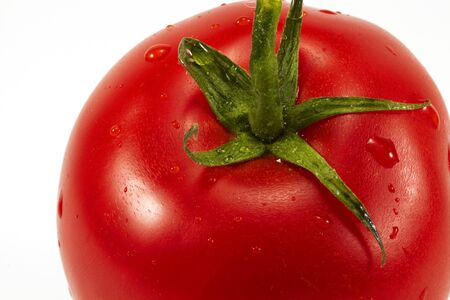 Close-up single tomato with waterdrops, isolated on white. Stock Photo