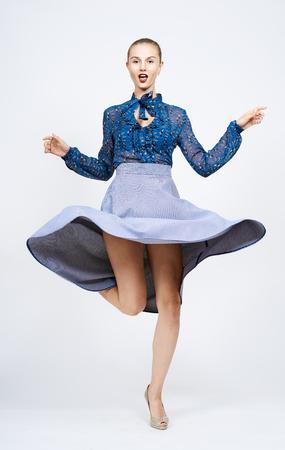 Young woman dancing in blue dress.