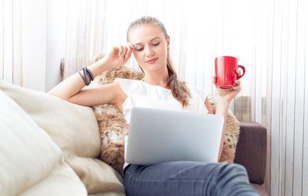 Young woman reading online on laptop. Stock Photo