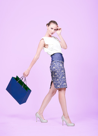 Young woman shopping with blue bag. Stock Photo