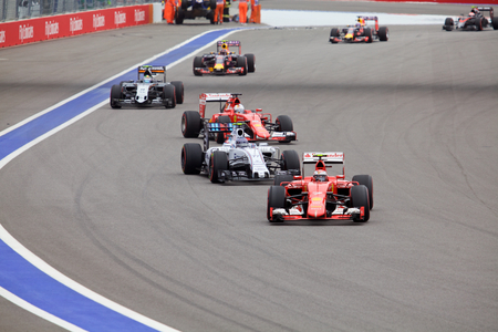 formule: Sochi, Russia - October 11, 2015: Kimi Raikkonen Scuderia Ferrari and Valtteri Bottas Williams Martini Racing warming their tires at the race of Formula One Russian Grand Prix at Sochi Autodrom.