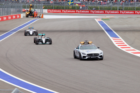 formule: Sochi, Russia - October 11, 2015: Lewis Hamilton of Mercedes AMG Petronas F1 team leads behind the FIA Safety Car at the race of Formula One Russian Grand Prix at Sochi Autodrom. Editorial