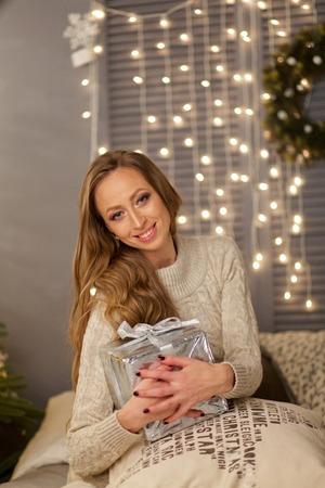 Beautiful girl sitting on bed with gift box. Interior of bedroom decorated for Christmas and holidays.