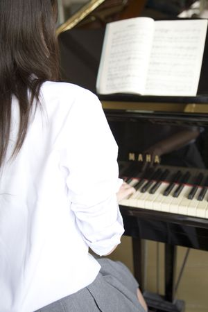 schoolroom: Back figure of high school girl playing the piano