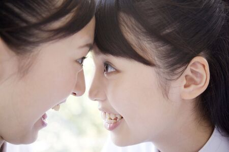 attaching: Women attaching forehead each other Stock Photo