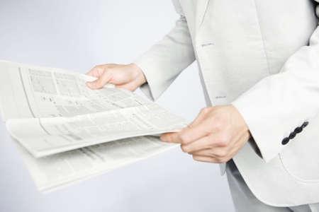 新聞を読むサラリーマンの手