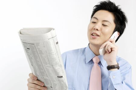 ビジネスマンの携帯電話で呼び出すと、新聞を見て 写真素材
