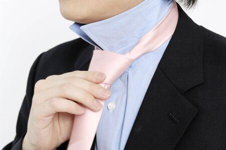 necktie: businessman putting on a necktie Stock Photo