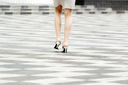 backview: Foot of business lady walking