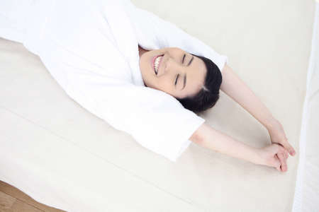 house robe: Woman stretching on the bed