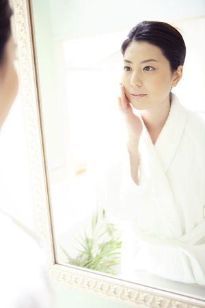 powder room: Woman looking at herself in a mirror Foto de archivo