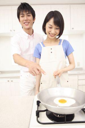 echtgenoot: Vrouw die een gebakken ei met haar man Stockfoto