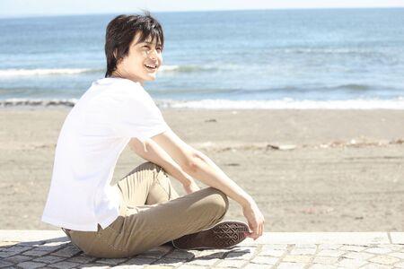 ビーチに座っていた日本人男性 写真素材