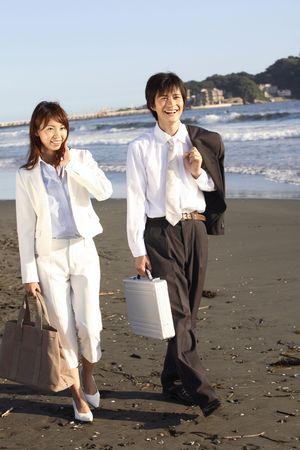 attache case: Japanese couple walking along a beach