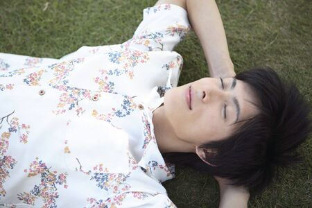 man lying down: Japanese man lying down on the grass Stock Photo