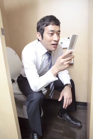 potable: Japanese office worker checking cell phone in a restroom Stock Photo