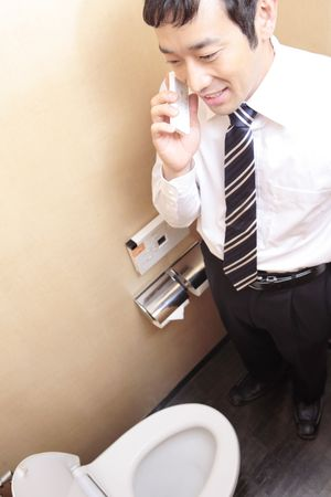 phon: Japanese office worker talking with cell phon in a rest room Stock Photo