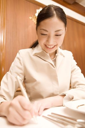 writing implements: Japanese woman taking memo Stock Photo