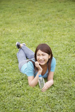 Woman who is lain at the grass Stock Photo