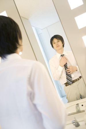 Office worker putting on a necktie in rest room