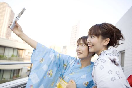 unlined: Japanese girls shooting a photo by cell phone