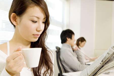 新聞を読んで日本のオフィスの女性