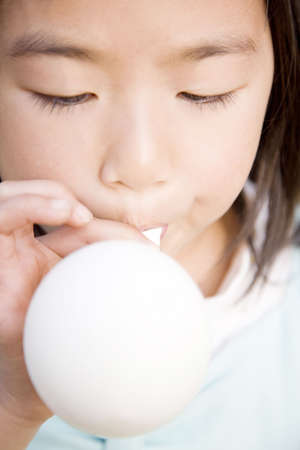 girl blowing: Japanese girl blowing up balloon