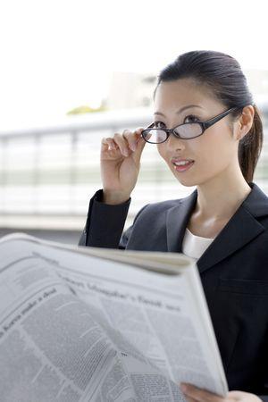 新聞を読むビジネス女性