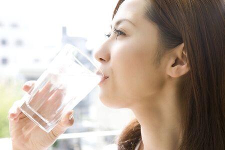 vasos de agua: Mujer japonesa que bebe un agua Foto de archivo