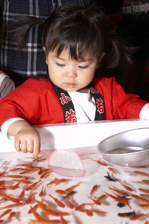 babyhood: Scooping goldfish Stock Photo