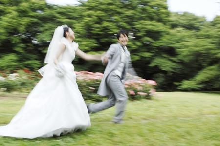 bridal couple: Bridal couple running in garden Stock Photo