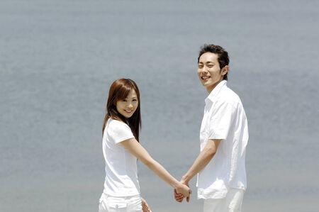 he and she: Couple walking the seaside Stock Photo