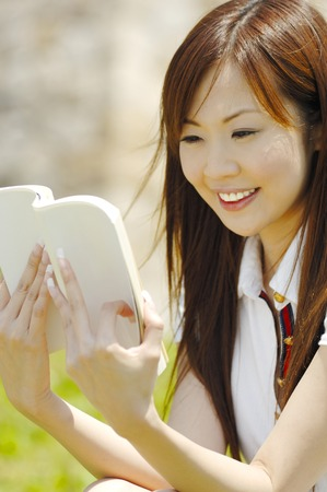 Japanese woman reading a book in the park photo