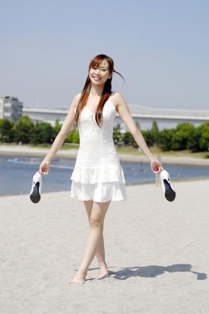手で靴を持つ歩行の女性 写真素材