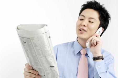 携帯電話を呼び出すと、新聞を見ている実業家