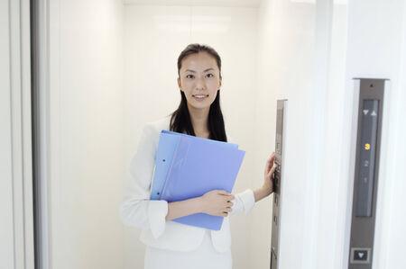 エレベーターの中で立っている女性のビジネス