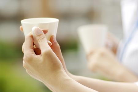 コーヒー カップを持っている女性の手