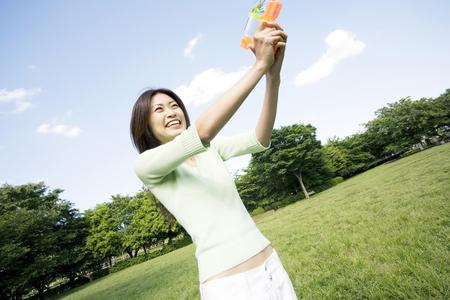 water gun: Woman playing with water gun