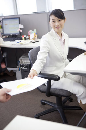 fellow: Office lady handing documents to a fellow worker Stock Photo