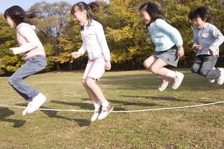 japanese children: Japanese children skip a rope in the park