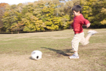 Japanese boy playing soccer photo