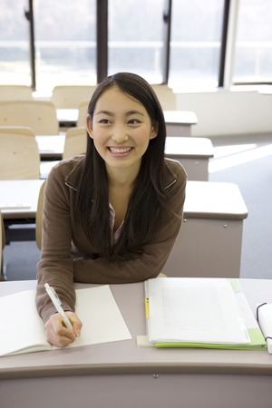 writing implements: Japanese female student studying in a classroom