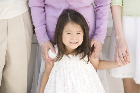 3 generations: Girl surrounded by adult Stock Photo