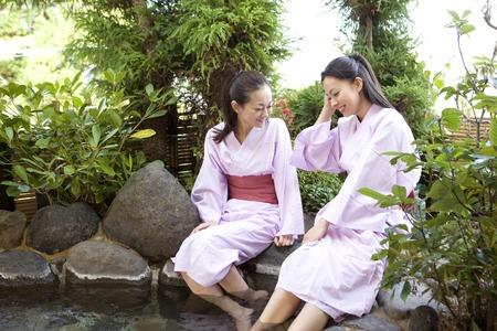 soak: 2 women to soak your feet on the open-air bath Stock Photo