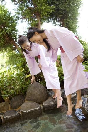 2 women to soak your feet on the open-air bath Фото со стока