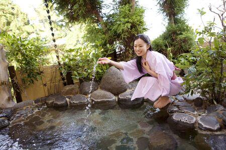 Las mujeres ven la aceleración de agua caliente del baño al aire libre